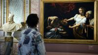"""Une femme devant le tableau du peintre italien Le Caravage """"Judith décapitant Holopherne"""" à Rome, le 30 septembre 2009 [VINCENZO PINTO / AFP/Archives]"""