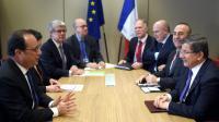 Le president français François Hollande (g) rencontre le Premier ministre turc Ahmet Davutoglu (d) et le ministre des Affaires étrangères Mevlut Cavusoglu (2e à d), à Bruxelles le 18 mars 2016 [STEPHANE DE SAKUTIN / POOL/AFP]