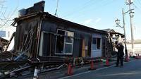 """Un """"touriste"""" photographie une des maisons abandonnées de Namie, dans la région de Fukushima, le 11 février 2016, 5 ans après l'accident nucléaire [TORU YAMANAKA / AFP]"""