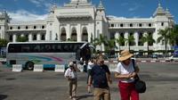 Des touristes marchant devant la mairie de Rangoun, le 12 octobre 2017 [Ye Aung THU / AFP/Archives]
