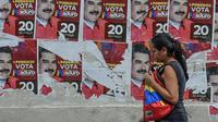 Une femme devant des affiches de campagne du président vénézuélien Nicolas Maduro, à Caracas le 19 mai 2018 [Juan BARRETO / AFP]