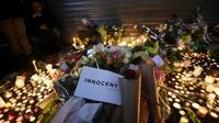 """Gerbes et bougies d'hommages déposées devant la """"Belle Equipe"""", au lendemain des attentats du 13 novembre 2015 à Paris [LIONEL BONAVENTURE / AFP/Archives]"""