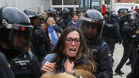 Des Catalans tentent d'aller voter malgré le blocage d'un bureau de vote par la garde civile.