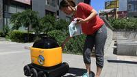Une femme récupère ses provisions acheminées par un robot livreur au cours d'une démonstration à Pékin, le 28 juin 2018 [GREG BAKER / AFP/Archives]