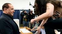 """Une militante Femen saute sur une table devant Silvio Berlusconi, , proclamant sur son torse nu """"Berlusconi, tu es périmé"""", le 4 mars 2018 dans un bureau de vote à Milan [Miguel MEDINA / AFP]"""