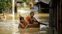 Des enfants dans une rue inondée le 18 décembre 2015 à Candaba aux Philippines [NOEL CELIS / AFP]
