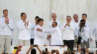 Le président colombien Juan Manuel Santos (G au centre serre la main du chef des Farc, Timoleon Jimenez, alias Timochenko (D au centre) scellant l'accord de paix historique [Luis ACOSTA / AFP]