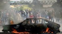 Des manifestants brûlent une voiture sur une route pour dénoncer la hausse des prix du diesel à Ribeirao das Neves au Brésil, le 25 mai 2018 [DOUGLAS MAGNO / AFP]