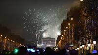 Des fêtards assistent à un spectacle pyrotechnique au-dessus du monument de l'Arc de Triomphe, sur l'avenue des Champs-Élysées, lors du nouvel an du 1er janvier 2017 à Paris.