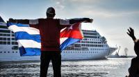 Un homme déploie un drapeau cubain à l'arrivée du premier paquebot américain, le 2 mai.