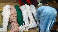 Un habitant enveloppe des cadavres avec des linceuils après une attaque de bandits dans la province de Zamfara au Nigéria, le 18 juin 2013 [STR / AFP/Archives]