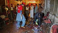 Les autorités et des volontaires sur le site de l'attaque suicide à Peshawar, le 10 juillet 2018 [ABDUL MAJEED / AFP]