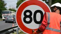 Un employé de la Direction interdépartementale des routes (DIR) installe un panneau de limitation de vitesse à 80 km/h sur une route nationale [PASCAL PAVANI / AFP/Archives]