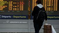 Un passager regarde un tableau d'affichage des vols à l'aéroport Roissy Charles-de-Gaulle, près de Paris lors d'une grève le 26 janvier 2016 [KENZO TRIBOUILLARD / AFP/Archives]