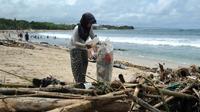 Une femme collecte des déchets plastiques sur une plage, le 9 décembre 2018 à Bali [SONNY TUMBELAKA / AFP]