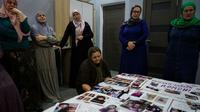 Des grands-mères des régions musulmanes du Caucase russe qui cherchent leurs familles parties avec l'EI montrent des photos de leurs proches dans un hôtel de Moscou, le 25 septembre 2017 [Naira DAVLASHYAN / AFP]