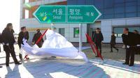 Un panneau indiquant les directions de Séoul et de Pyongyang dévoilé lors d'une cérémonie d'inauguration des travaux de connexion des réseaux ferroviaires et routiers entre les deux Corées, le 26 décembre 2018 à Kaesong, en Corée du Nord [KOREA POOL / KOREA POOL/AFP]