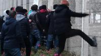 Capture d'écran d'une video de Taranis News en date du 24 janvier 2016, de migrants défonçant une clôture pour monter sur un ferry à Calais [- / TARANIS NEWS/AFP/Archives]