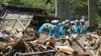 Des équipes de secouristes recherchent des survivants, le 13 juillet 2018 à Sakacho, au Japon [JIJI PRESS / JIJI PRESS/AFP]