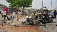 Des somaliens transportent le cadavre d'une victime après un attentat à Mogadiscio le 9 avril 2017 [Mohamed ABDIWAHAB / AFP]