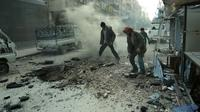 Des hommes constatent les dégâts après un bombardement du régime sur Douma, la principale ville de l'enclave rebelle dans la Ghouta orientae, le 10 mars 2018 [HAMZA AL-AJWEH / AFP]