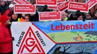 Des ouvriers de l'usine Bombardier brandissent des panneaux au logo du syndicat allemand de la métallurgie IG Metall, à Hennigsdorf près de Berlin (nord-est), le 8 janvier 2018 [Bernd Settnik / dpa/AFP]