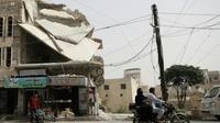Une homme roule sur une motocyclette devant un bâtiment endommagé dans la ville de Binnish, dans le nord de la province d'Idleb en Syrie, le 15 octobre 2018 [OMAR HAJ KADOUR / AFP]