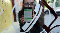 Nina Kov, l'une des développeuses à l'origine de l'application InfoAid, montre l'une de ses pages sur son smartphone, le 14 septembre 2015 à Röszke, en Hongrie [ATTILA KISBENEDEK / AFP]