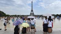 Des touristes devant la Tour Eiffel [Miguel Medina / AFP/Archives]