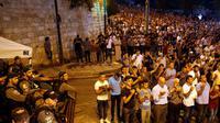Des forces de sécurité israéliennes regardent des Palestiniens prier à l'extérieur de l'esplanade des Mosquées à Jérusalem, le 24 juillet 2017 [Ahmad GHARABLI / AFP]