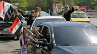 Des Syriens manifestent leur soutien au régime de Bachar el-Assad, le 14 avril 2018 dans les rues de Damas après les raids aériens des Occidentaux contre des sites militaires [STRINGER / AFP]