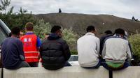 Des migrants attendent aux côtés d'un employé de l'Office français de l'immigration et de l'intégration le 16 août 2017 à Calais [PHILIPPE HUGUEN / AFP/Archives]