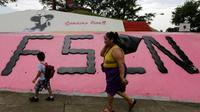 Une femme et un enfant marche devant un monument à la mémoire du révolutionnaire Augusto C. Sandino, à Managua, le 17 juillet 2018 [Inti OCON / AFP/Archives]
