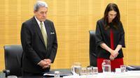 La Première ministre néo-zélandaise Jacinda Ardern et le vice-Premier ministre Winston Peters observent une minute de silence à la mémoire des victimes de l'éruption volcanique du 9 décembre, lundi 16 décembre au Parlement néo-zélandais à Wellington [Hagen Hopkins / POOL/AFP]