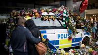 Des personnes se recueillent devant un véhicule de police recouvert de fleurs sur le site d'un attentat au camion-bélier, le 10 avril 2018 à Stockholm [Jonathan NACKSTRAND / AFP/Archives]