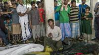 Des Rohingyas se recueillent devant les corps de réfugiés morts dans un naufrage en venant chercher refuge au Bangladesh, le 29 septembre 2017 près de la plage d'Inani, à Cox's Bazar [FRED DUFOUR / AFP]