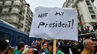 """Un manifestant à Alger brandit une pancarte sur laquelle on peut lire """"Pas mon président"""", le 13 décembre 2019 [RYAD KRAMDI                         / AFP]"""