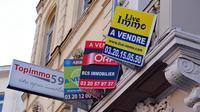 Des panneaux d'agences immobilières sur la façade d'un immeuble où un appartement est à vendre [Philippe Huguen / AFP/Archives]