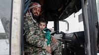 Un combattants rebelle syrien évacué de la ville de Doumeir, au nord-est de Damas, tient dans les bras son fils dans un bus arrivant à Azaz, dans le nord du pays le 20 avril 2018 [Sameer Al-Doumy / AFP]