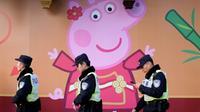 Des policiers passent devant l'effigie de Peppa Pig sur un mur, le 25 janvier 2019 à Shanghai [Matthew KNIGHT / AFP/Archives]
