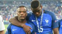 Patrice Evra (g) et Paul Pogba (d) quittent la pelouse du Stade de France dépités après la défaite des Bleus face au Portugal en finale de l'Euro-2016 [PATRIK STOLLARZ                      / AFP/Archives]