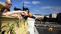Jets de fleurs dans le Danube à l'endroit de la collision mortelle entre un bateau de croisière et une embarcation transportant des touristes sud-coréens, le 1er juin à Budapest [Peter Kohalmi / AFP]