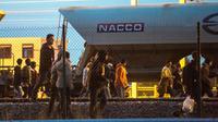 Des migrants marchent sur la voie ferrée en direction du terminal d'Eurotunnel le 11 août 2015 à Fréhun [Philippe Huguen / AFP/Archives]