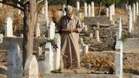 Un Syrien lit le coran sur les tombes de proches et de membres de sa famille au premier jour de l'Aïd al-Adha, la grande fête musulmane du sacrifice, le 1er septembre 2017 à Binnish (Syrie) [Omar haj kadour / AFP]