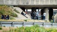 Des migrants au bord d'une route près du Port de Calais, dans les Hauts-de-France, le 3 juillet 2017 [DENIS CHARLET / AFP/Archives]