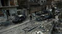 Photo prise le 25 février 2018 montrant un homme marchant dans une rue de la ville de Douma au milieu de voitures détruites et immeubles endommagés après des raids aériens du régime syrien sur la Ghouta orientale, une enclave rebelle près de Damas bombardée par le régime syrien [HAMZA AL-AJWEH / AFP]