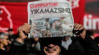 """Un manifestant brandit un exemplaire du quotidien d'opposition """"Cumhuriyet"""" devant le siège du journal à Istanbul le 2 novembre 2016 [YASIN AKGUL / AFP/Archives]"""