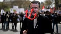 Un manifestant portant un masque à l'effigie d'Emmanuel Macron défile avec des avocats, des magistrats et des greffiers à Paris le 11 avril 2018, contre le projet de réforme de la justice [Lionel BONAVENTURE / AFP]
