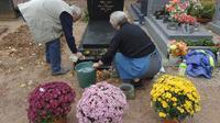 Un couple entretient la tombe d'un proche le 26 octobre 2006 dans un cimetière de Caen [Mychele Daniau / AFP/Archives]