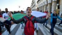 Un manifestant avec un drapeau algérien proteste contre un éventuel 5e mandat du président algérien Abdelaziz Bouteflika, le 22 février 2019 à Alger [RYAD KRAMDI                         / AFP]